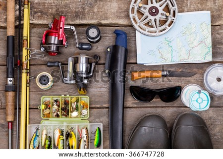 different fishing tackles for journey on background of wooden boards