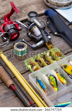 different fishing tackles for journey on background of wooden boards - stock photo