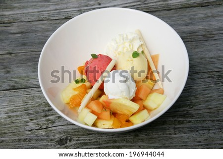 Different flavours of ice cream in a bowl with some fruit and chocolate sticks. - stock photo