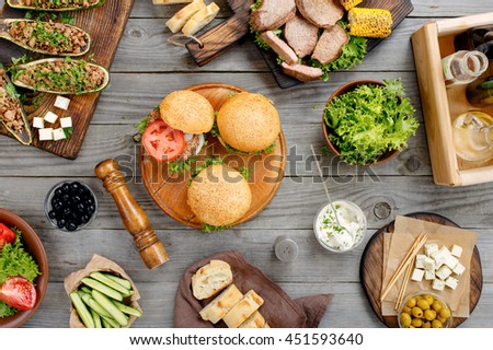 Different food on a wooden table, burgers, steak and eggplant stuffed with meat cooked on the grill, salad, vegetables, sauces and cheese with olives, top view. Outdoors food Concept - stock photo