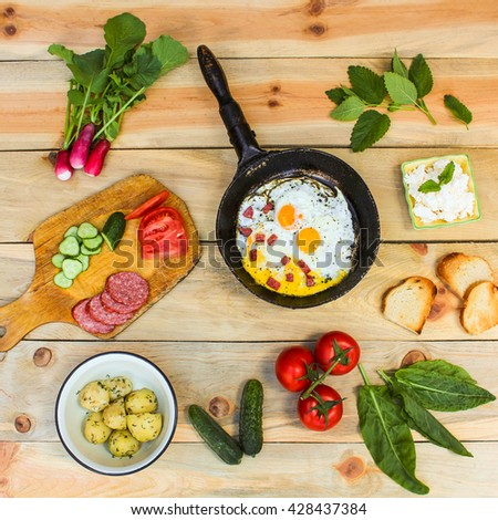 Different food: scrambled eggs in frying pan, boiled potatoes, curd, croutons, radishes, cucumbers, tomatoes, smoked sausage, croutons, mint, sorrel on wooden table. Toned image  - stock photo