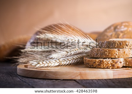Different fresh baked breads on board with golden wheat ears on wooden rustic table - stock photo