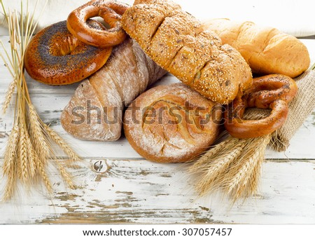 Different fresh bread and wheat on a wooden table.