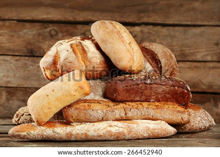Different fresh bread on old wooden table - stock photo