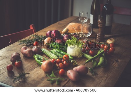 Different fresh farm vegetables on wooden table. Wine bottles and bread on background. Autumn harvest and healthy organic food concept. Toned picture - stock photo