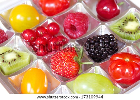 different fresh fruits in a chocolate box - Diet concept - stock photo