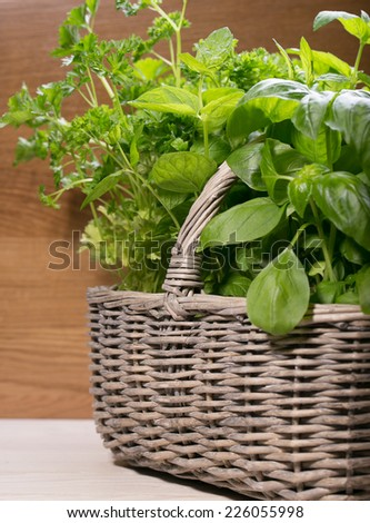 Different fresh herbs in basket on wooden background - stock photo