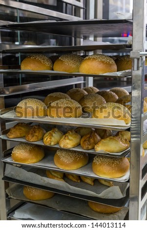 different fresh hot buns in handcart from oven - stock photo