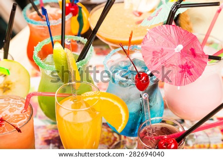 different freshness cocktails with ice in glasses with drinking straw and umbrellas - stock photo