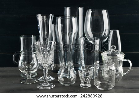 Different glassware on dark color wooden background - stock photo