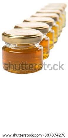 Different grade and color of honey in mason jar over white background