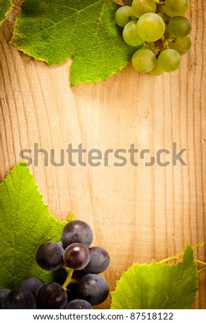 Different grapes with green leaves on wooden table - stock photo