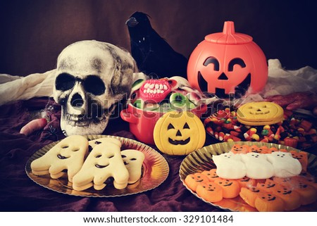 different Halloween candies and cookies on a table decorated with some scary ornaments, such as a skull, a black crow or a carved pumpkin - stock photo