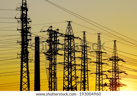 different high voltage pylons on yellow background - stock photo