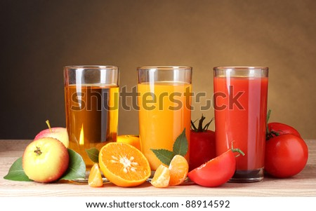 Different juices and fruits on wooden table on brown background - stock photo