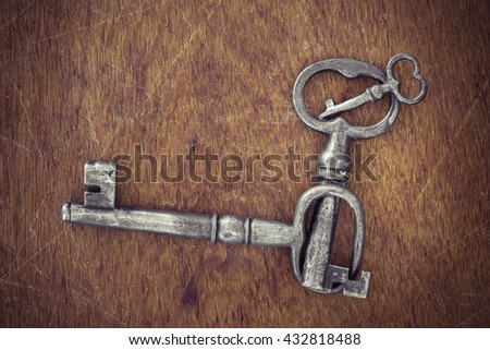 Different keys in old vintage retro style on wooden surface. Set of three from small to large. Symbol of safety, variety and difference.