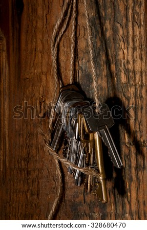 Different keys on thread over wooden surface - stock photo