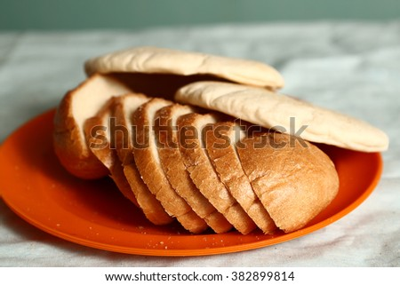 different kind of bread tortilla cake loaf sliced pie on the orange plate - stock photo