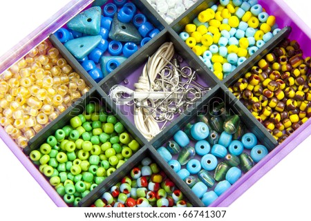 Different kind of colorful beads close up on a white background - stock photo