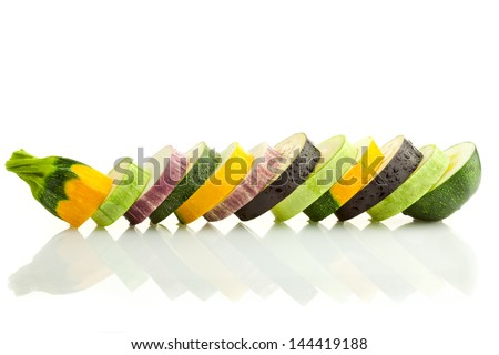Different kind of courgettes (zucchini) and eggplants / colorful slices / horizontal border isolated on white with real reflection - stock photo