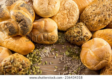 Different kind of freshly baked bread and rolls on wooden table - stock photo