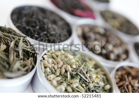 Different kind of green tea in a little box on white - stock photo