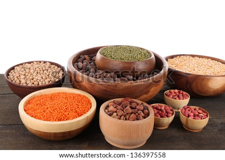 Different kinds of beans in bowls on table isolated on white