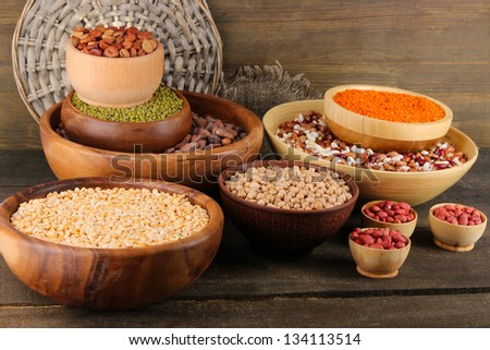 Different kinds of beans in bowls on wooden background