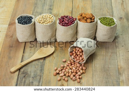 Different kinds of beans in sacks bag, focus on scattered peanut - stock photo