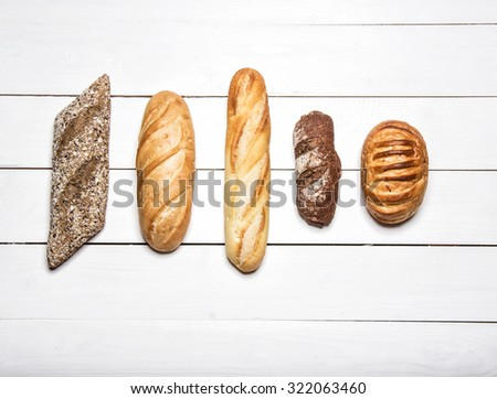 Different kinds of bread on white wooden table  - stock photo