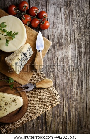 Different kinds of cheese on rustic wooden table