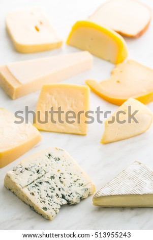 Different kinds of cheeses on kitchen table.
