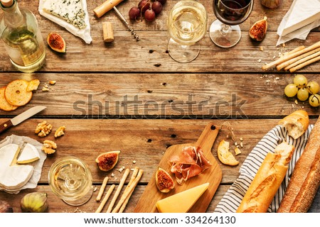 Different kinds of cheeses, wine, baguettes, fruits and snacks on rustic wooden table from above. French tasting party or feast scenery. Layout with free text space.  - stock photo