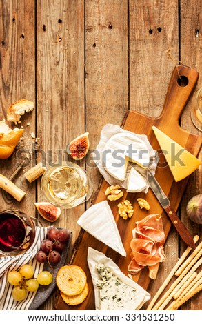 Different kinds of cheeses, wine, baguettes, fruits and snacks on rustic wooden table from above. French tasting party or feast scenery. Background layout with free text space.  - stock photo