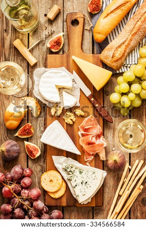 Different kinds of cheeses, wine, baguettes, fruits and snacks on rustic wooden table from above. French tasting party or feast scenery. - stock photo