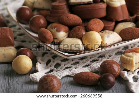 Different kinds of chocolates on plate on wooden table - stock photo