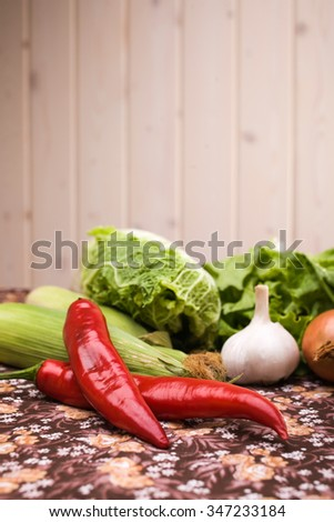 Different kinds of fresh juicy vegetables sweet corn cob chinese cabbage hot red peppers garlic lettuce natural ingridients for healthy lifestyle indoor on light background closeup copyspace, vertical - stock photo