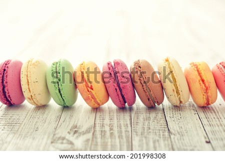 Different kinds of macaroons in stack on light wooden background - stock photo