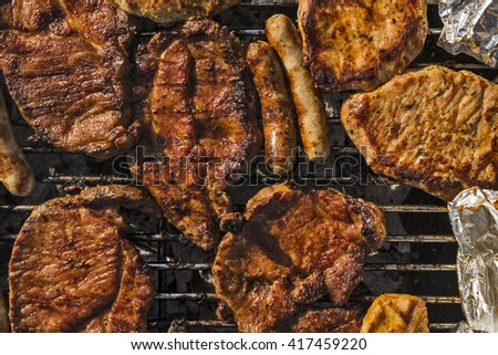 different kinds of meat and sausages on a barbecue grill seen from top view - stock photo