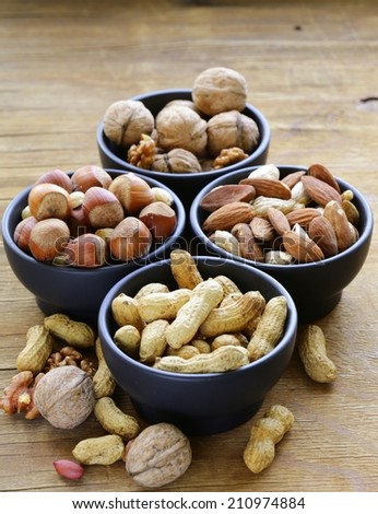 different kinds of nuts (almonds, walnuts, hazelnuts, peanuts) in a bowl on a wooden table