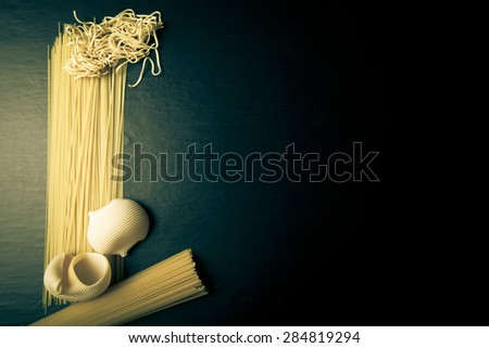 Different kinds of pasta on a black background. Space for text. Toned. - stock photo