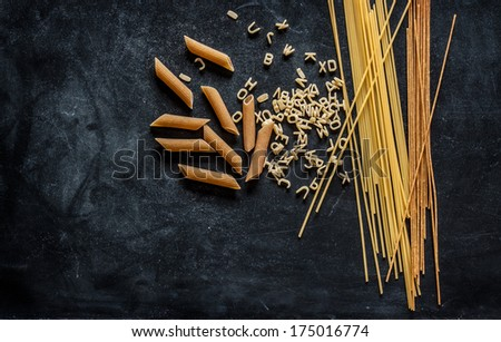 Different kinds of pasta on black chalkboard. Menu background with free text space. - stock photo