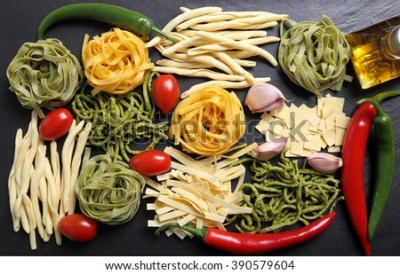 Different kinds of pasta on the black ceramic background. - stock photo