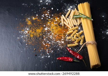 Different kinds of pasta, red chili pepper, rosemary, sea salt and spices on a black background. selective focus. - stock photo