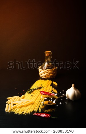 Different kinds of pasta, red chili pepper, rosemary, sea salt and spices on a black background. Selective focus. Toned. - stock photo