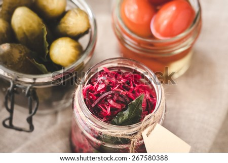 Different kinds of pickles - cabbage with beetroot, cucumbers and tomatoes in small jars