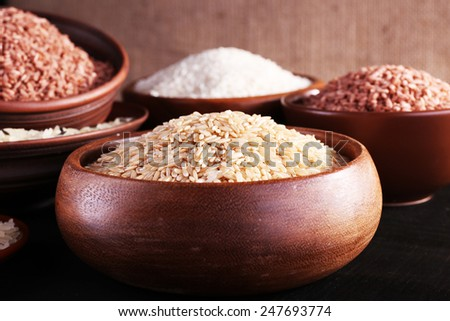 Different kinds of rice in bowls on table on sackcloth background - stock photo