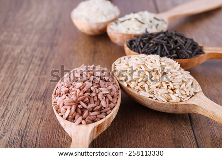 Different kinds of rice in spoons on wooden background - stock photo