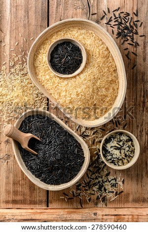 Different kinds of rice in wooden bowls - gold and black wild rice - stock photo