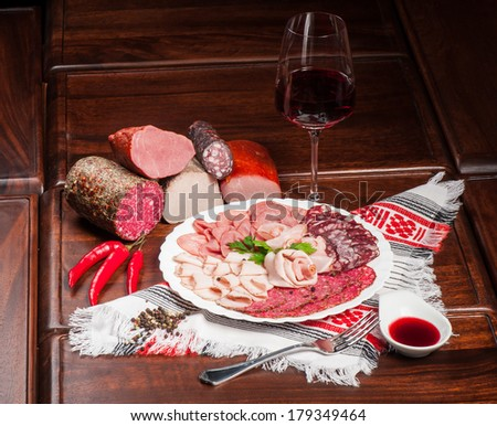 Different kinds of sliced sausages served with red wine - stock photo